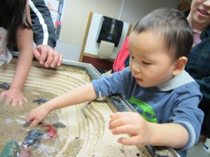 Tai loved splashing at the table where he could build a stream bed.