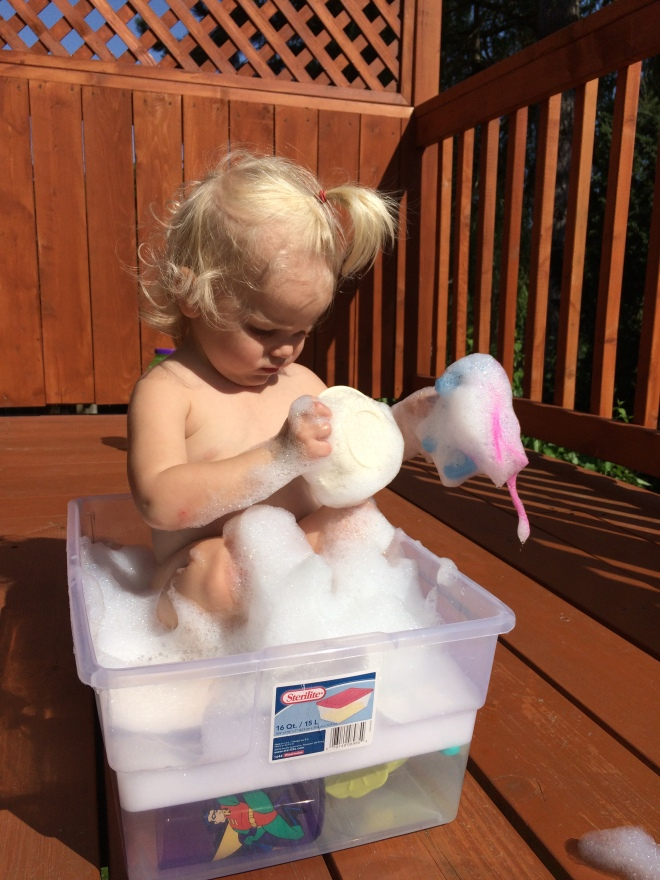 toddler playing on deck bubbles