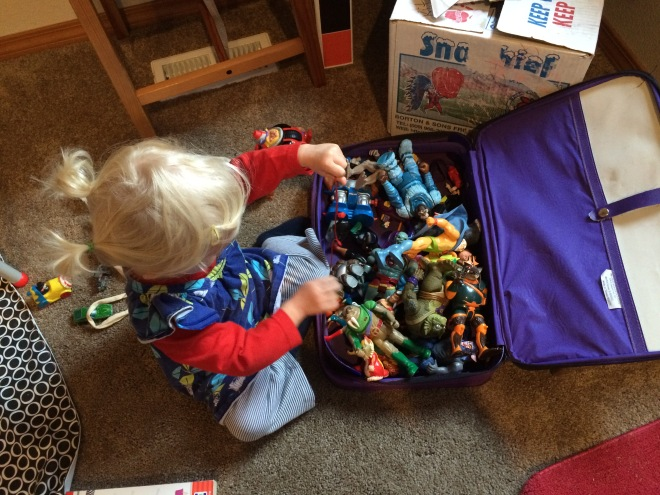 Toddler playing with Thundercats Batman action figures
