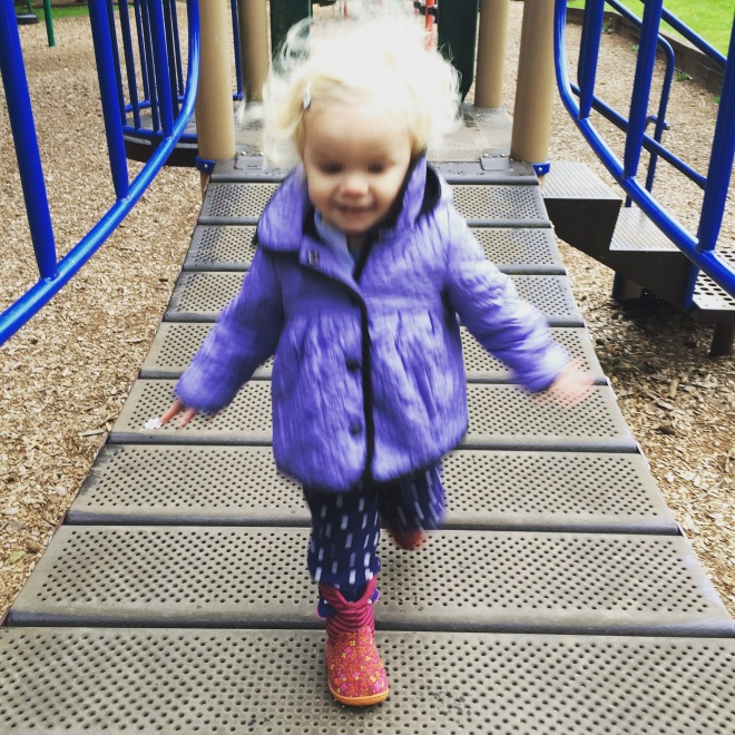Toddler running on bridge playground